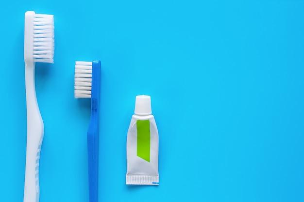 青色の背景に歯を洗浄するために使用される歯磨き粉と歯ブラシ