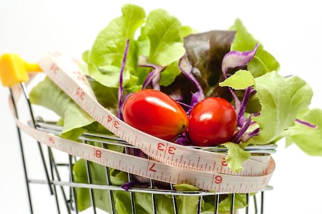 白い背景の上の測定テープとショッピングカートの野菜