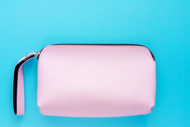 青色の背景にピンクの女性革バッグ