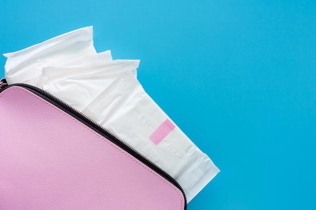 青色の背景に女性のピンクのバッグの生理用ナプキン