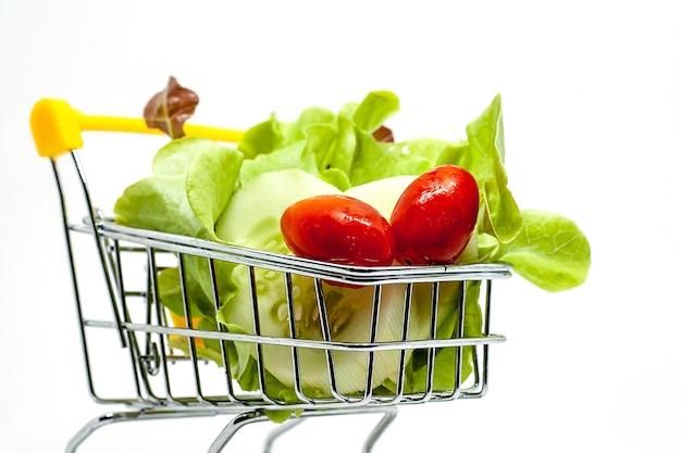 白い背景の上のショッピングカートに新鮮な野菜