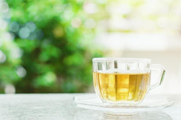 自然の緑の背景をぼかした写真に対してお茶のカップ