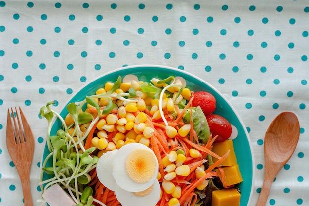 Салат из свежих овощей с вареным куриным яйцом, деревянной ложкой и вилкой на синей ткани в горошек или на фоне скатерти