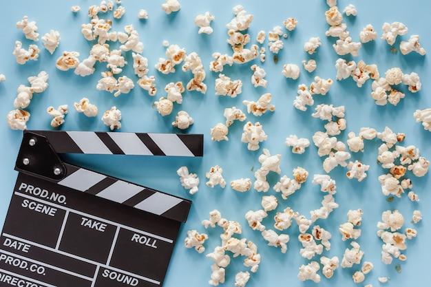 エンターテイメントの概念のための青のポップコーンと映画クラッパーボード