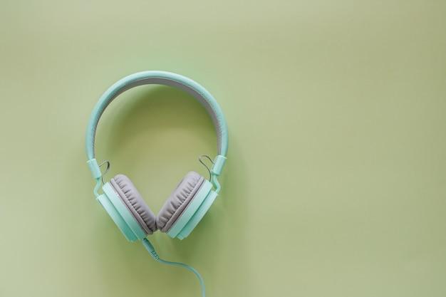 音楽とリラクゼーションのための緑の背景のヘッドフォン