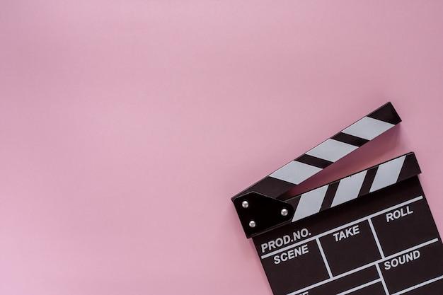 撮影機器のピンクの背景の映画クラッパーボード