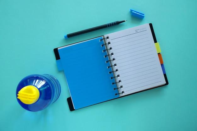 Раскрытая тетрадь с ручкой и бутылка с водой на сини для концепции здорового образа жизни