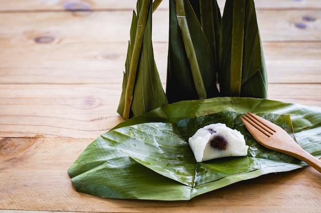 タイのデザートコンセプトの木製の表面に甘いココナッツの詰め物と蒸し小麦粉カスタード