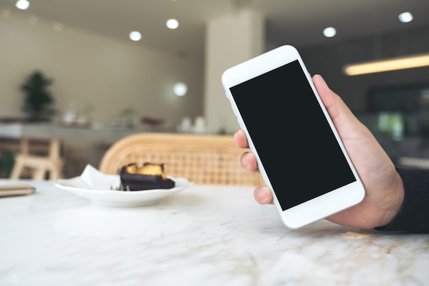 Рука, проведение белый мобильный телефон с пустой черный рабочий стол в кафе