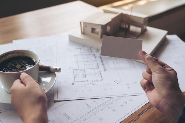 Рука, держащая и показывающая пустую визитную карточку с моделью архитектуры