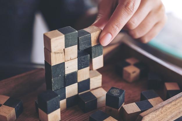 Макрофотография изображение людей, играющих и строительство деревянных головоломки