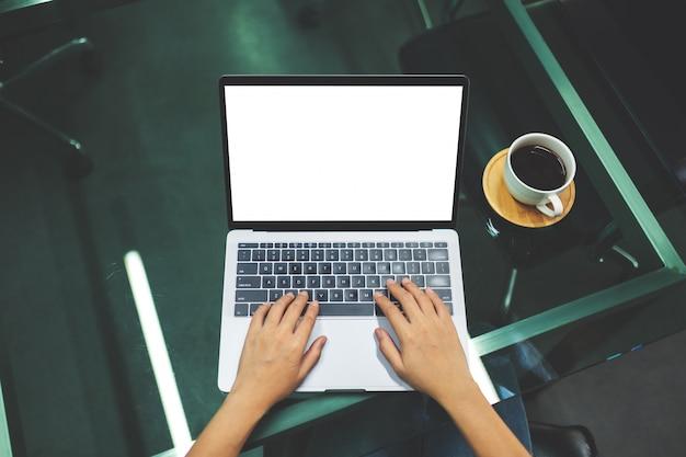 Взгляд сверху коммерсантки используя и печатая на портативном компьютере с пустым белым экраном настольного компьютера, кофейной чашкой на столе в офисе