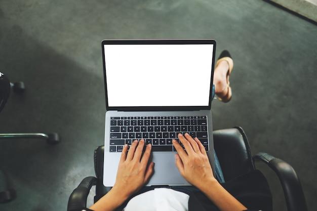 Взгляд сверху коммерсантки используя и печатая на портативном компьютере с пустым белым экраном настольного компьютера в офисе