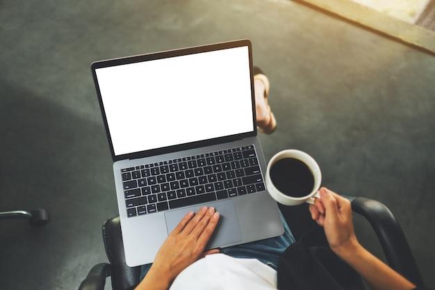 Взгляд сверху женщины используя и касаясь на сенсорной панели портативного компьютера с пустым белым экраном рабочего стола пока выпивающ кофе