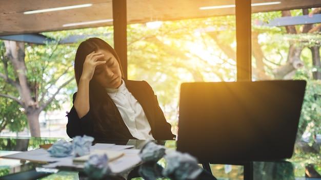 実業家はオフィスでの仕事で問題を抱えている間テーブルに台無しにされた紙とラップトップでストレスを感じる