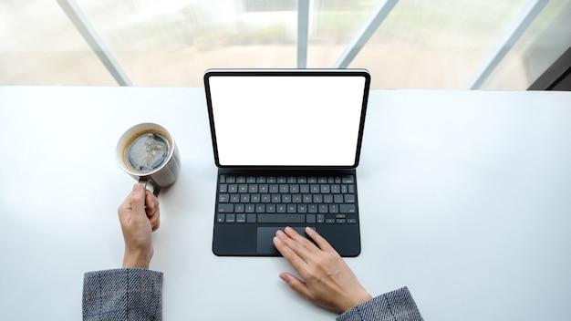 Взгляд сверху женщины используя и касаясь на сенсорной панели таблетки с пустым белым экраном настольного компьютера как пк компьютера пока выпивающ кофе