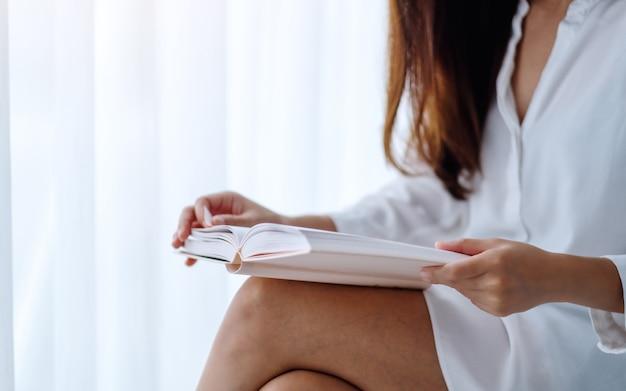 自宅の寝室で本を読んで美しいアジアの女性のクローズアップ