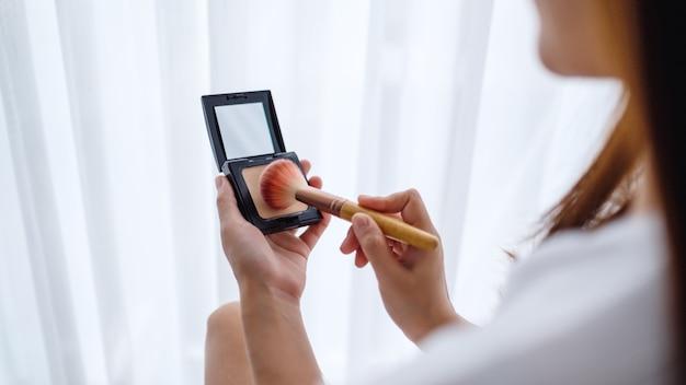 寝室のブラシでメイクアップパウダーを適用する美しい女性のクローズアップ