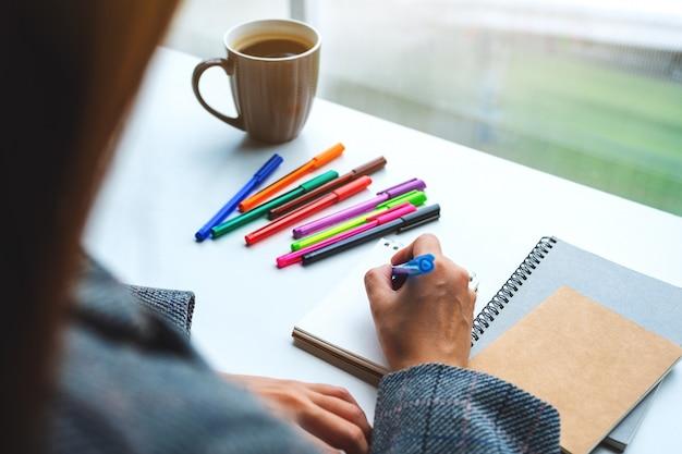Макрофотография женщины, писать на пустой блокнот с цветными ручками и чашка кофе на столе