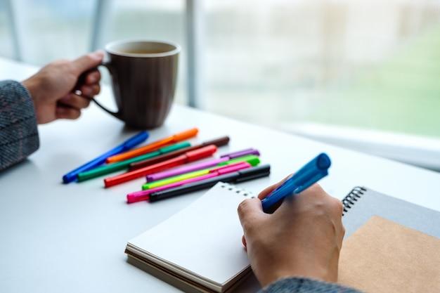 Крупный план сочинительства женщины на пустой тетради с покрашенными ручками пока выпивающ кофе