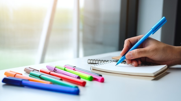 Макрофотография женщины, писать на пустой блокнот с цветными ручками на столе