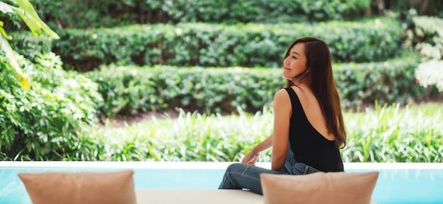 Портрет красивой молодой азиатской женщины любил сидеть у бассейна с зеленой природой