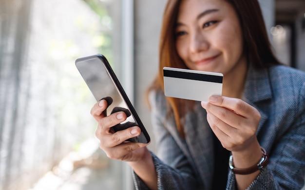クレジットカードを使用して携帯電話でオンラインで購入およびショッピングする美しいアジアの女性