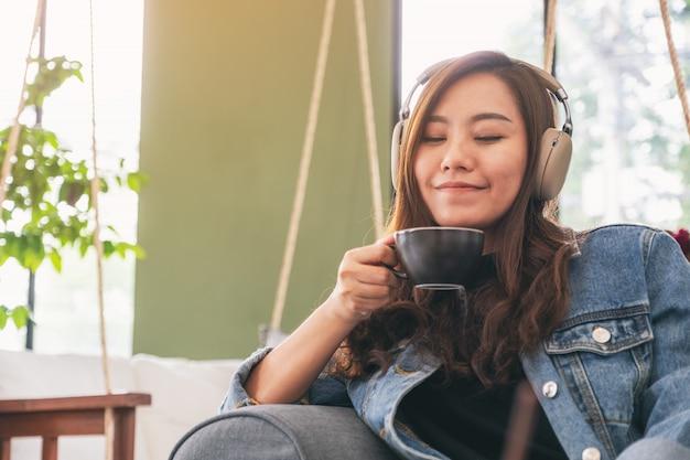 Красивая азиатская женщина слушая музыку с наушниками пока выпивающ кофе с чувствовать счастливым и расслабленным в кафе