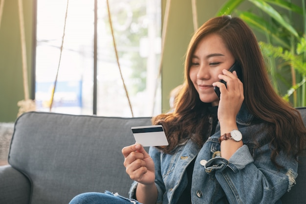 携帯電話で話しながらオンラインでの購入やショッピングにクレジットカードを使用しているアジアの女性