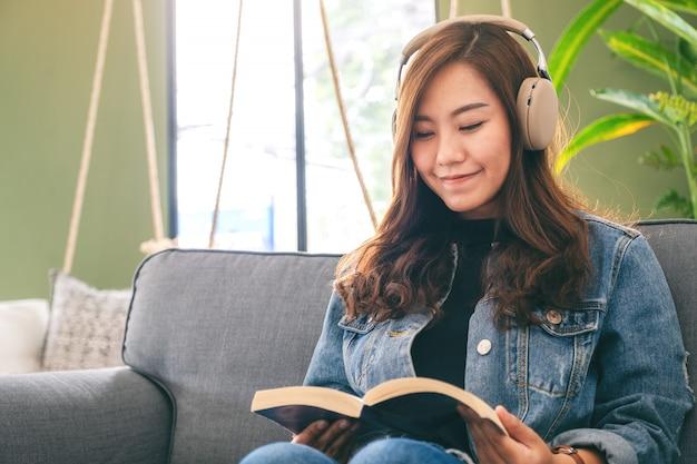 美しいアジアの女性は本を読みながらヘッドフォンで音楽を聴いて楽しむ