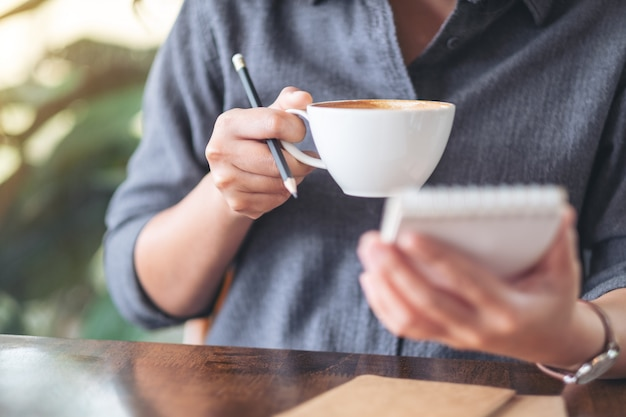 Женщина держит тетрадь и чашку кофе