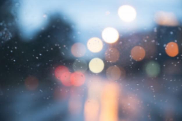 雨が降っている夜の車のライトの画像をぼかします