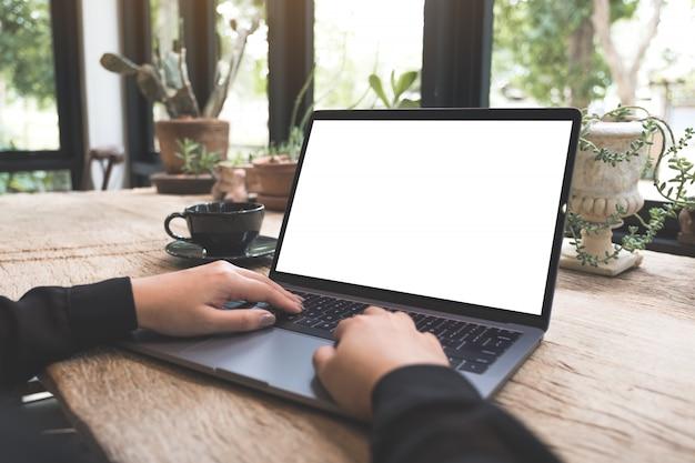 Макет изображения женщины с помощью и набрав на ноутбуке с пустой белый экран рабочего стола на деревянный стол в кафе