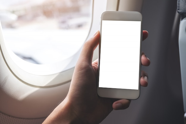 Макет изображения руки, держащей белый смартфон с пустым экраном рабочего стола рядом с окном самолета