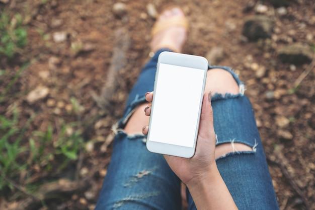 Вид сверху макет изображения женщины, держащей белый мобильный телефон с пустым экраном рабочего стола, сидя на земле на открытом воздухе