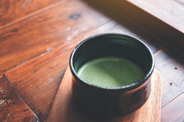 Чашка горячего матча латте на деревянный пол