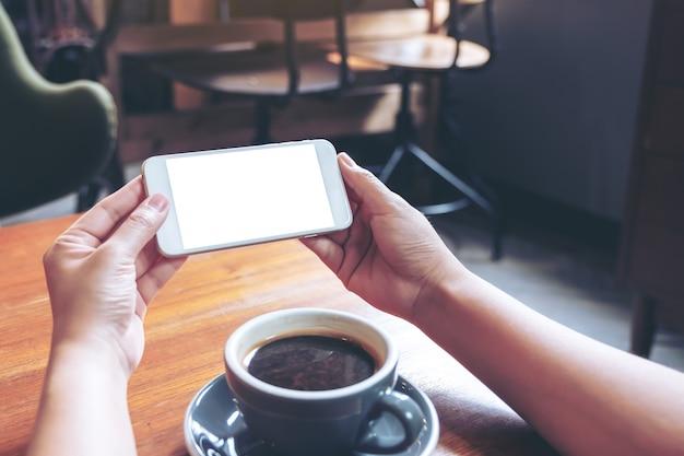 Макет изображения руки, держащей и использующей белый мобильный телефон с пустым экраном горизонтально для просмотра с чашкой кофе на деревянном столе