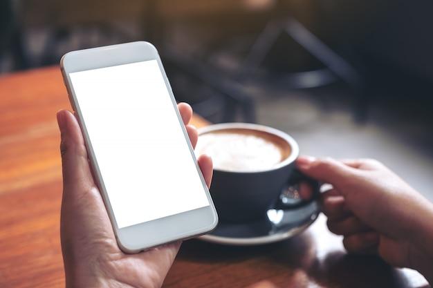 Макет изображения руки, держа белый мобильный телефон с пустым экраном, попивая кофе в современном кафе