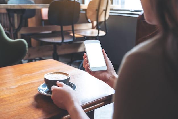 Макет изображения женщины, держащей белый мобильный телефон с пустым экраном, попивая кофе в современном кафе