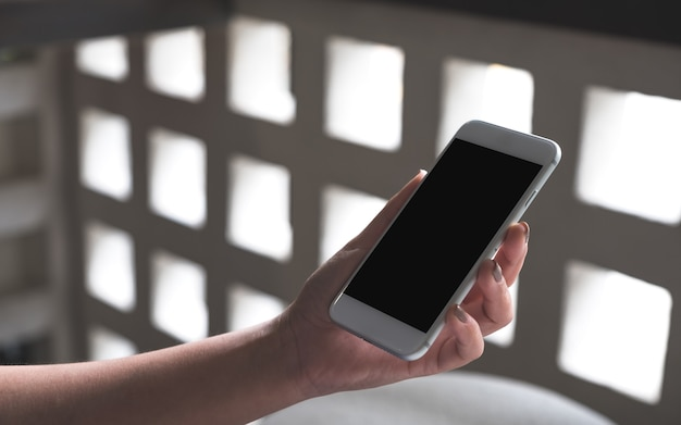 Макет изображения женских рук, держа белый мобильный телефон с пустым экраном рабочего стола в кафе