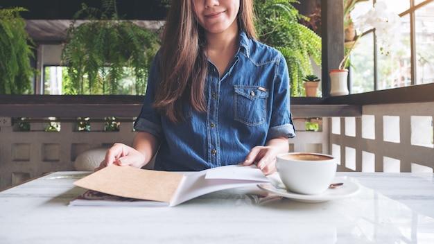 Крупным планом изображение женщины, открыв книгу с чашкой кофе на столе в современном кафе