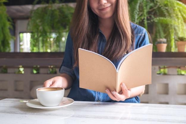 Изображение крупного плана красивой азиатской женщины читая книгу пока выпивающ кофе в современном кафе