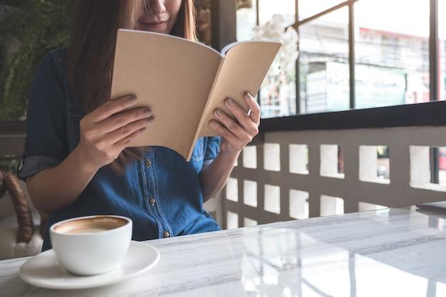 Крупным планом изображение женщины, читающей книгу с чашкой кофе на столе в современном кафе