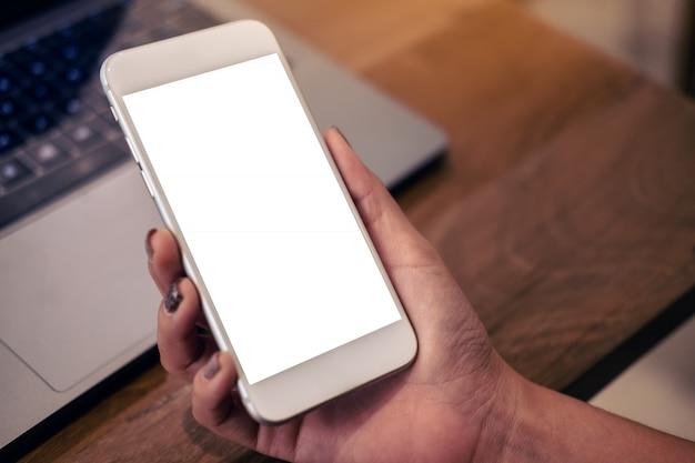Макет изображения руки, держащей мобильный телефон с пустой белый экран с ноутбуком на деревянный стол