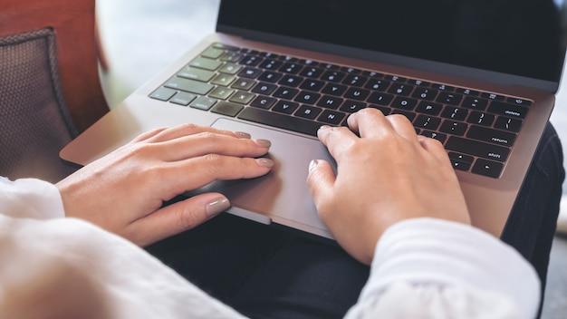 Женщина с помощью и набрав на ноутбуке с пустой белый экран рабочего стола