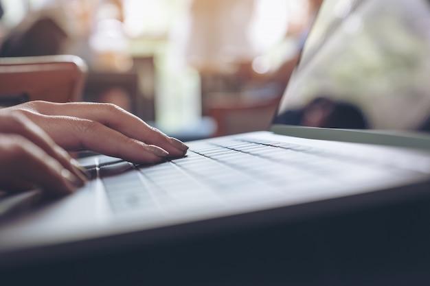 Макрофотография изображение рук с помощью и набрав на клавиатуре ноутбука