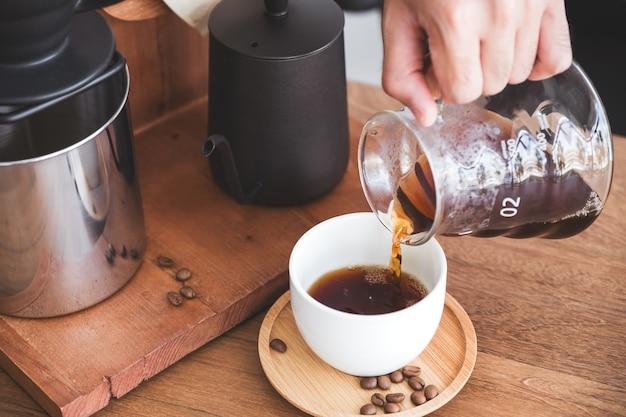 マグカップにドリップコーヒーを注ぐ手