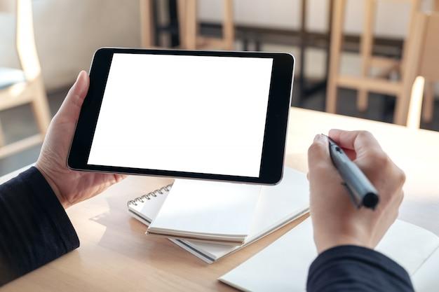 空白の白いデスクトップ画面で黒いタブレットを保持して使用する手