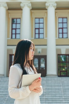 タブレットコンピューターを保持している美しい若いアジア女性