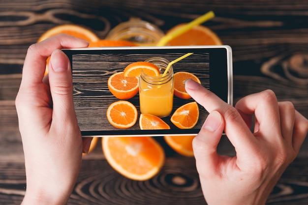 オレンジの写真を撮る手